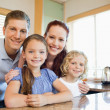 Family standing together behind the kitchen counter — Stock Photo