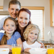 Family with breakfast behind the kitchen counter — Stock Photo