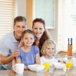 Family together with breakfast standing behind the kitchen count — Stock Photo