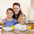 Mother with children and breakfast in the kitchen — Stock Photo