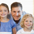 Smiling father with his children in the kitchen — Stock Photo
