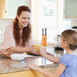 Stock Photo: Mother giving her daughter orange juice