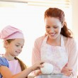 Cheerful mother and daughter preparing dough — Stock Photo #11211895
