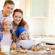 Family with baking ingredients behind the kitchen counter — Stock Photo