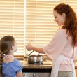 Royalty-Free Stock Photo: Mother showing her daughter what shes cooking