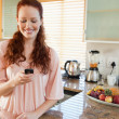 Woman writing text message in the kitchen — Stock Photo #11211989