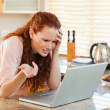 Woman looking annoyed at her laptop — Stock Photo