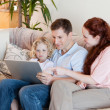 Family using laptop on the sofa — Stock Photo