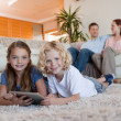 Brother and daughter using tablet on the carpet — Stock Photo