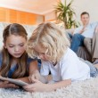 Siblings using tablet on the living room floor — Stock Photo
