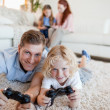 Father and son in the living room playing video games — Stock Photo #11212138