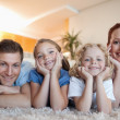 Cheerful family on the carpet — Stock Photo #11212147