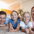 Cheerful smiling family on carpet — Stok Fotoğraf #11212150