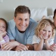 Stock Photo: Family lying on bed