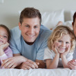 Family lying on the bed — Stock Photo