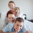 Playful family together on the bed — Stock Photo #11212262