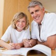 Boy getting help with homework from father — Stok fotoğraf