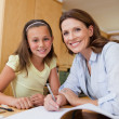 Mother helping daughter with homework — Stock Photo #11212360