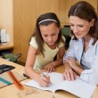 Girl doing homework with her mother — Stok fotoğraf