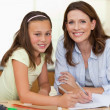 Woman helping her daughter with homework — Stock Photo