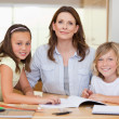 Stock Photo: Womhelping her children with homework