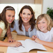 Foto Stock: Mother helping her children with homework