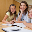 Mother doing homework with children — Stock Photo