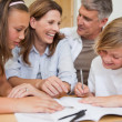 Siblings getting help with homework from parents — Stock Photo