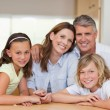 Family together behind table - Stock Photo