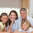 Smiling family behind kitchen table — Stock Photo