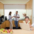Children with laptop in the kitchen and parents behind them — Stock Photo