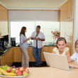 Stock Photo: Children with notebook in the kitchen and parents behind them