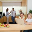 Siblings with laptop in the kitchen with parents behind them — Stock Photo