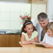 Man looking at tablet his children are using — Stock Photo