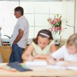 Stock Photo: Parents talking with children doing homework in front of them