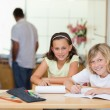 Siblings doing homework with their parents behind them - Stock Photo