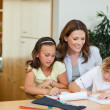 Mother having a look at children's homework — Stock Photo