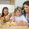 Woman making sandwiches with her children — Stock Photo