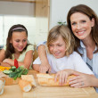 Stock Photo: Mother making sandwiches with her children