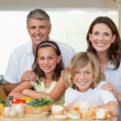 Smiling family making sandwiches — Stock Photo