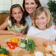 Smiling mother making sandwiches with her children — Stock Photo #11212488