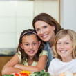 Smiling siblings and mother making sandwiches — Stock Photo #11212494