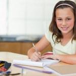 leende flicka göra läxor i köket — Stockfoto