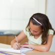 Girl writing in the kitchen — Stock Photo