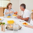 Woman serving dinner to hungry family — Stock Photo