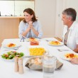 Family sitting at the dinner table - Stock Photo