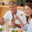 Laughing couple eating dinner — Stock Photo