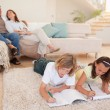 Stock Photo: Siblings doing homework on the floor with parents behind them