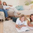 Siblings doing homework on the carpet with parents behind them — Stock Photo