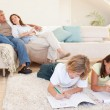 Brother and sister doing homework on the carpet — Stock Photo